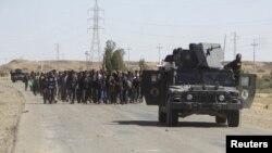 نیروهای امنیتی عراق در حال محافظت از شهروندانی هستند که خانههای خود را در پی درگیریها میان نیروهای امنیتی و داعش رها کردهاند و به اماکن موقتی انتقال داده میشوند