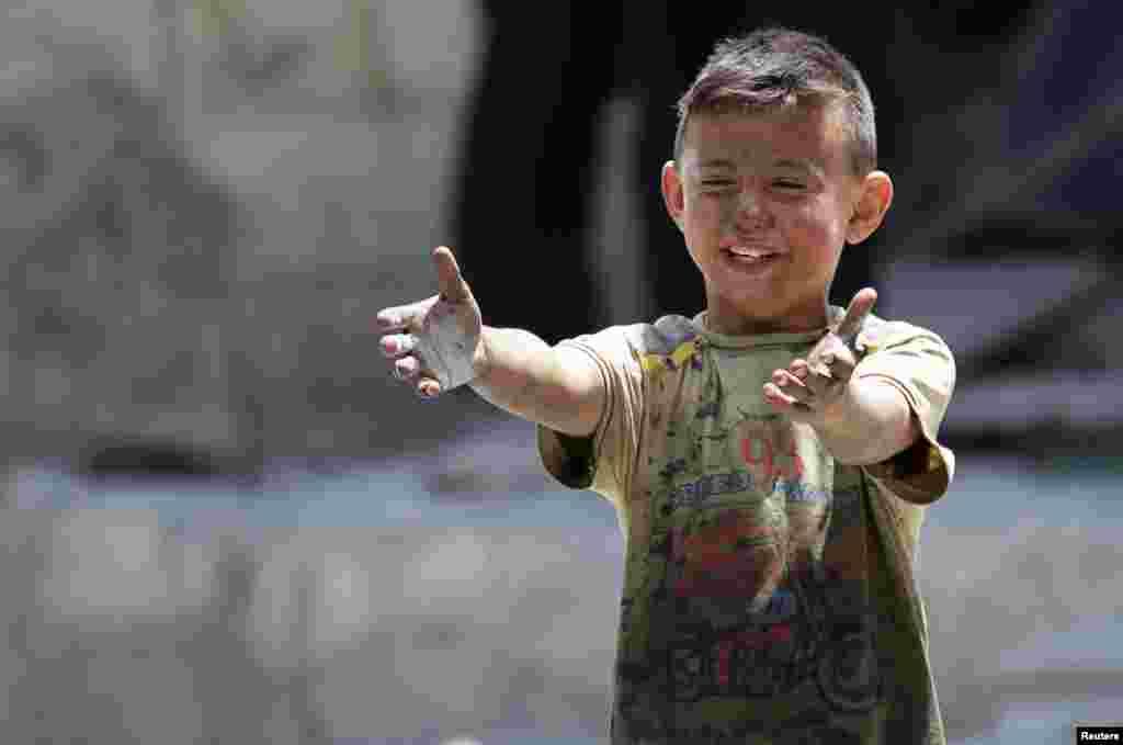 Howa zarbasynda dogany öldürilen oglan reaksiýa bildirýär. Maaret al-Numan şäheri, Idlib welaýaty, Siriýa. (Reuters/Khalil Ashawi)