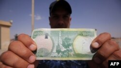 An Iraqi policeman holds a 10,000-Iraqi dinar note bearing an image of Mosul's leaning minaret, now destroyed.