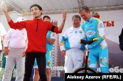 Артист цирка Мурат Мутурганов( слева) подарил Александру Винокурову одноколесный велосипед. Алматы, 16 сентября 2012 года.