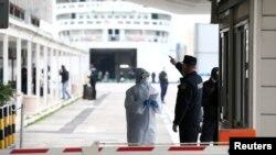 Policajac razgovara s medicinskim osobljem u blizini trajekta koji je iz Italije stigao u Split, 11. ožujka 2020. godine.
