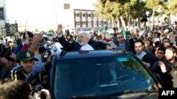 Швейцариядагы сүйлөшүүдөн кайтып келген Ирандын тышкы иштер министри Зарифти аэропортто котологон эл тосуп алды. 3-апрель, 2015-ж. Тегеран ш.