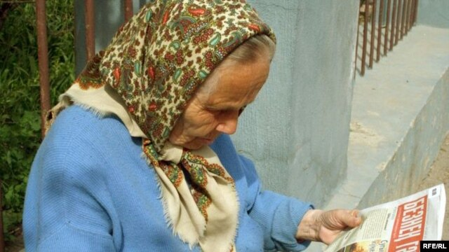 "Tatarstan -- Old tatar woman reads Tatar newspaper ""Beznen gacit"", 06May2009"