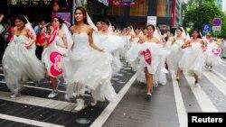 Девушки в свадебных платьях участвуют в «забеге невест», организованном в супермаркете. Гуанчжоу, 12 августа 2013 года.