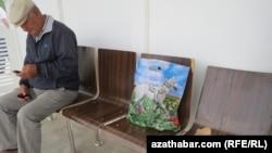 Мужчина с мобильным телефоном на автобусной остановке в Туркменистане. Иллюстративное фото.