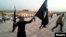 Вооруженный боевик группировки «Исламское государство» размахивает черным знаменем ИГ в Мосуле. 23 июня 2014 года.