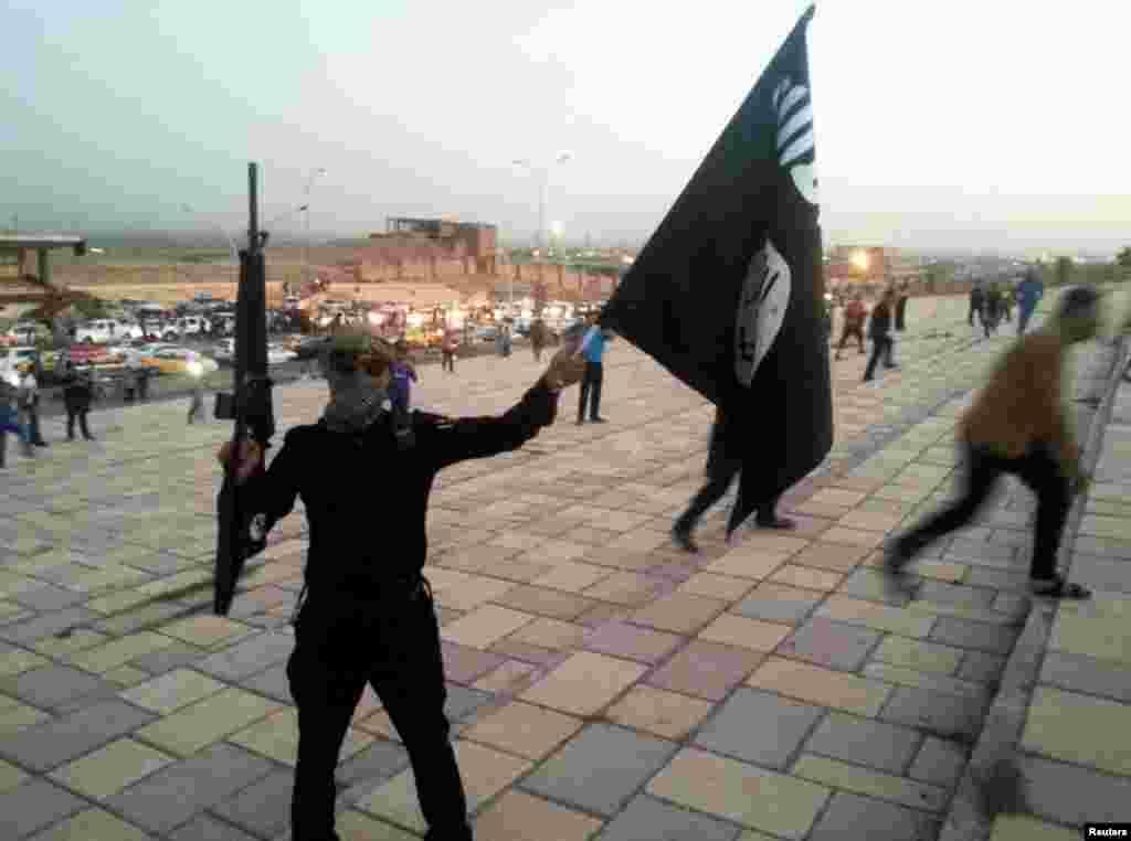 Боевики группировки захватили Мосул в начале июня 2014 года без особого труда. Почти два миллиона мирных жителей оказались заблокированы На фото – боевик ИГИЛа размахивает флагом группировки в Мосуле через две недели после захвата. 23 июня 2014