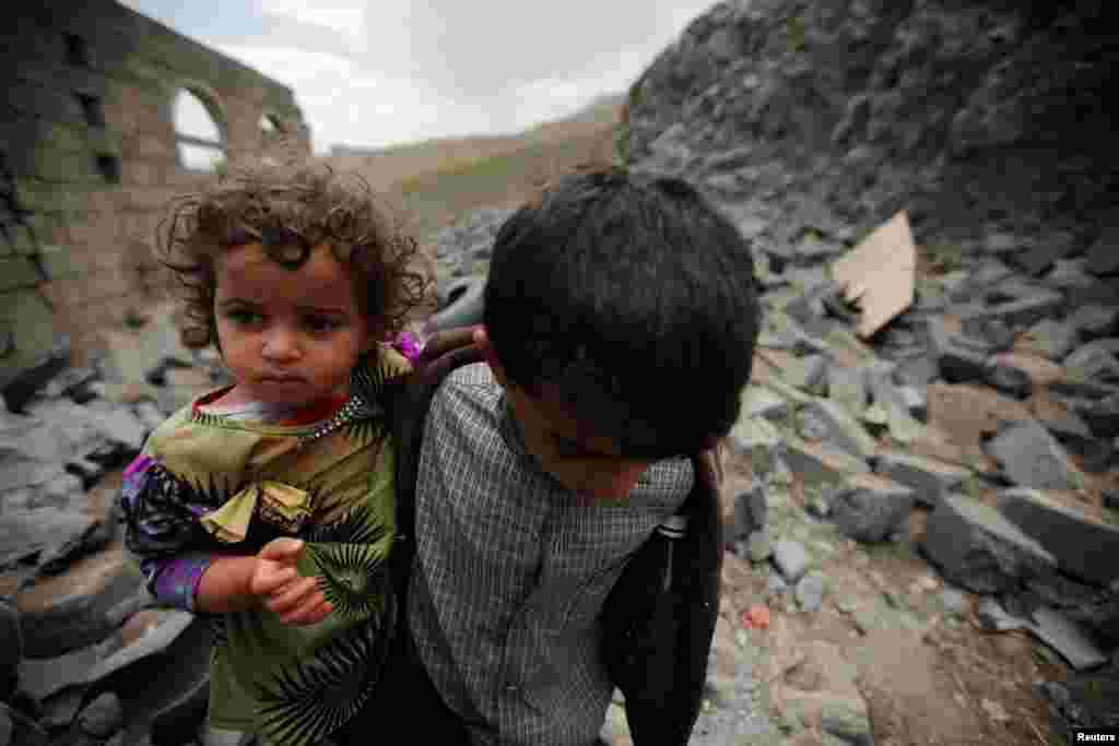 A boy carries his sister as he walks on the rubble of a house after it was destroyed by a Saudi-led air strike in Yemen's capital, Sanaa. (Reuters/Mohamed al-Sayaghi)