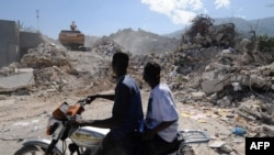 Men watch the demolition of a collapsed building in Port-au-Prince