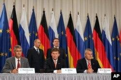 Володимир Путін та Ґергард Шредер стоять позаду Олексія Міллера (в центрі), Юрґена Гамбрехта (ліворуч) та Вульфа Бернотата (праворуч) під час церемонії підписання документів про енергетичне співробітництво між Росією та Німеччиною. Берлін, вересень 2005 року