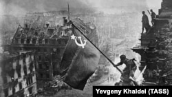 A staged photograph of Soviet soldiers raising the hammer-and-sickle flag above the building after it was seized remains one of the most iconic photographs to emerge from World War II, known in Russia as the Great Patriotic War.