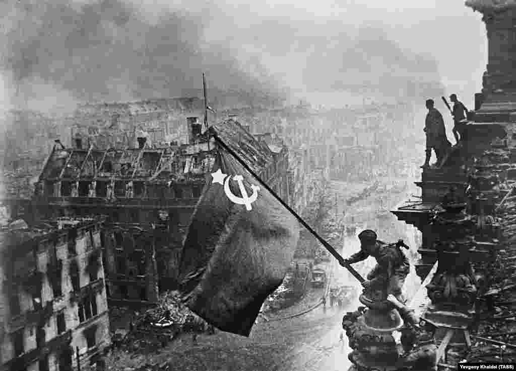 A Red Army soldier hoisting the Soviet flag above the Reichstag in Berlin on May 2, 1945. The photo would become both the defining image of the Red Army's victory over Nazi Germany and an example of the deception of Soviet propaganda.