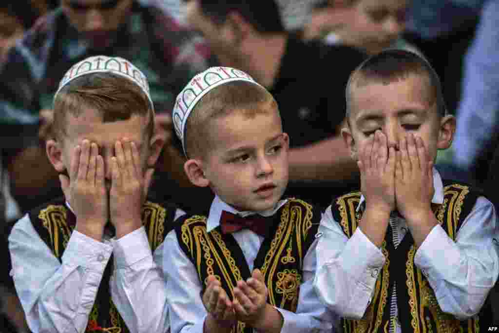 Young Kosovar Muslims take part in a prayer during a celebration of Eid al-Fitr, which marks the end of the fasting month of Ramadan, at the Sulltan Mehmet Fatih mosque in Pristina. (AFP/Armend Nimani)