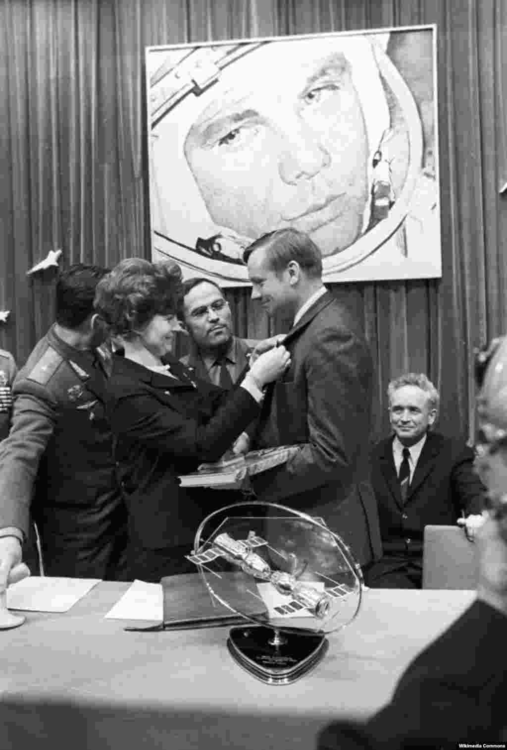 Tereshkova pins a badge on U.S. astronaut Neil Armstrong during his visit in 1970 to the Soviet training center, Star City. More than 500 people from 38 countries have traveled into space.