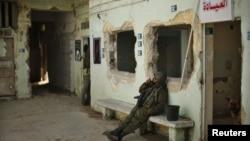 Një palestinez me uniformen ushtarake izraelite qëndron i ulur brenda në burgun që forcat izraelite e kanë përdorur në Gaza për të mbajtur të burgosurit gjatë okupimit izraelit të Rripit të Gazës, 11 Prill 2013
