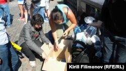 Волонтеры сортируют гуманитарную помощь по пакетам, чтобы доставить ее в Крымск