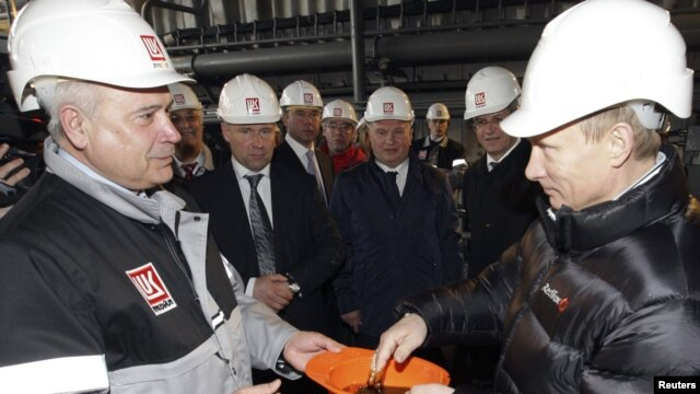 Prime Minister Vladimir Putin (right) dips his hand into a hardhat full of oil. Critics say he's likely delighted by international crises that have increased the value of Russia's chief export.