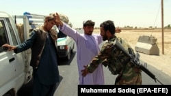 Afghan soldiers search people at a checkpoint on a highway leading to the Maiwind district of restive Kandahar Province on October 19.
