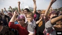 Etiraz aksiyasına öz körpəsi ilə gələn ana tutulan ərinin azadlığa buraxılmasını tələb edir, Urumçi, 7 iyul 2009
