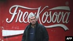 Albanac prolazi pored grafita na zidu zgrade u Kosovskoj Mitrovici