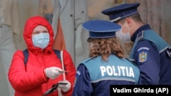 Жена показва документите си на полицията, която контролира спазването на карантината в Букурещ, намиращ се на 360 км. от Сучава
