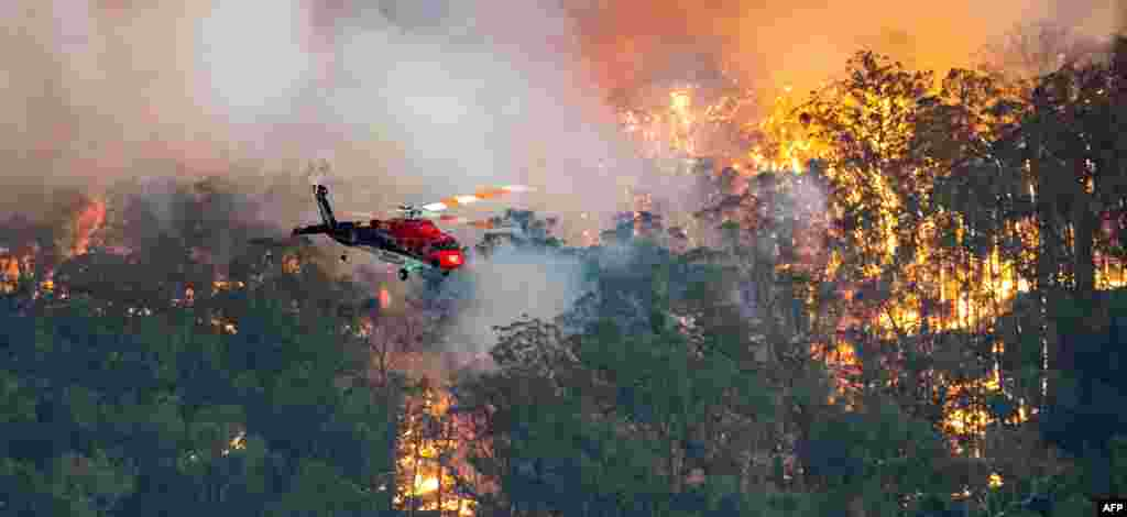 A helicopter fights a bushfire near Bairnsdale in Victoria's East Gippsland region in Australia. (AFP)