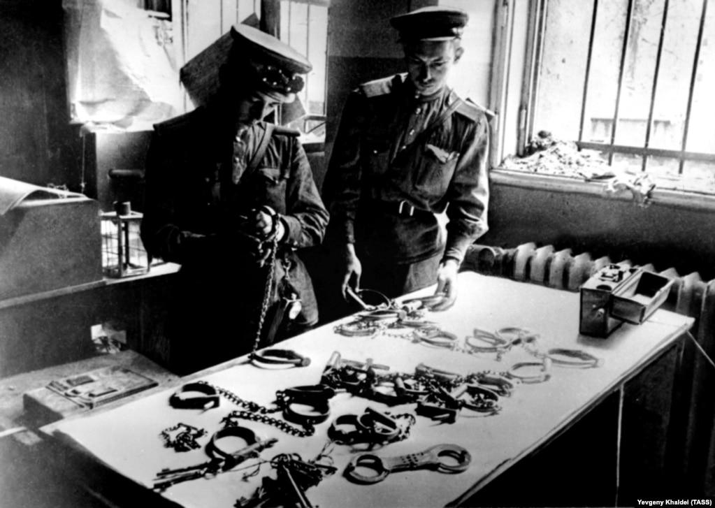 Советские солдаты рассматривают наручники, найденные в штаб-квартире Государственной тайной полиции (Гестапо) в Берлине.