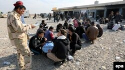 An Iraqi soldier speaks with displaced men from Mosul on November 27.