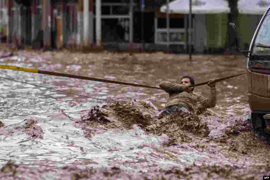 A man clings to a security line to cross a street flooded by the overflowing Copiapo River due to heavy rainfall that affected some areas in the city in Chile on March 26. (AFP)