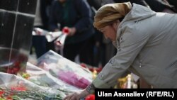 Қырғызстандағы Сәуір төңкерісі кезінде қаза тапқан азаматтар ескерткішіне гүл шоқтарын қойып жатқын әйел. Қырғызстан, Бішкек, 7 сәуір 2013 жыл.