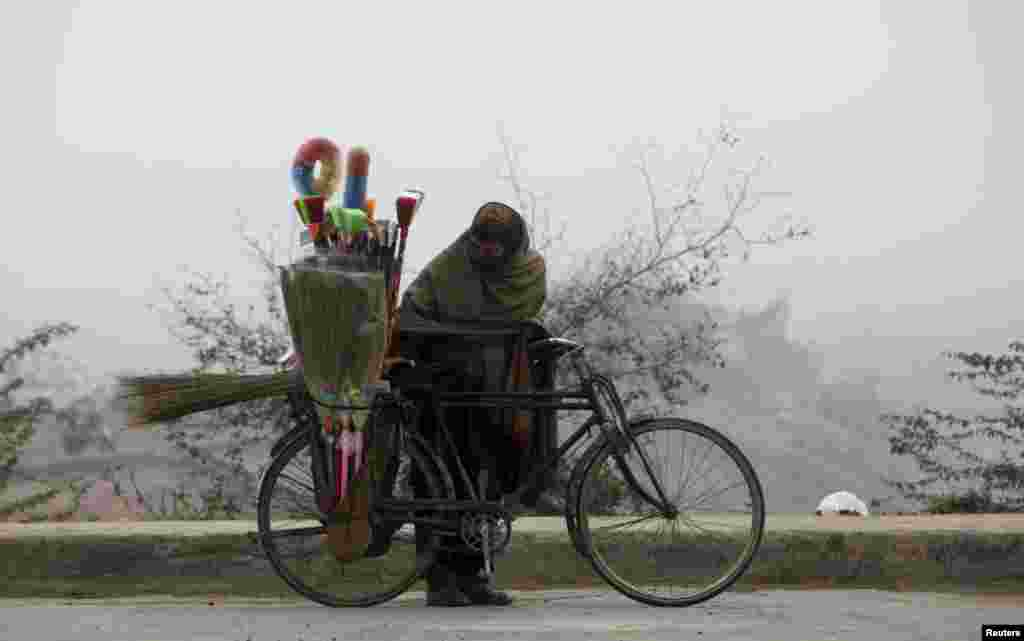 A brush salesman checks the load on his bicycle as he prepares to ride in the morning fog in Lahore, Pakistan. (Reuters/Mohsin Raza)
