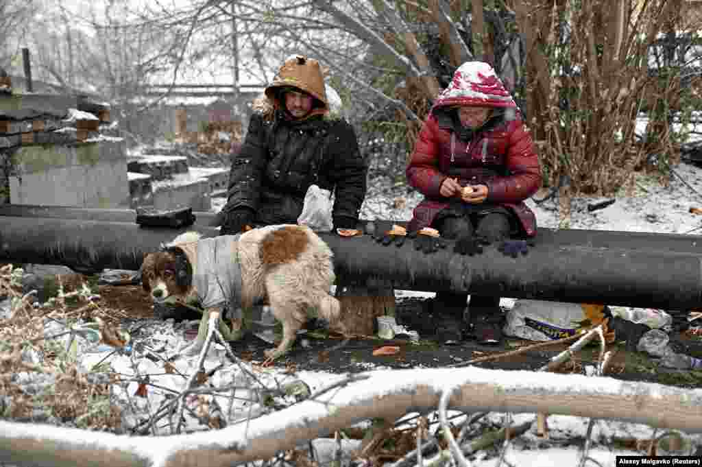 """Sasha, 49, nicknamed """"Poltorashka"""" (a 1 1/2-liter beverage bottle), and Lyusya Stepanova, 44, sit on a warm pipe with their dog, Bim, as they share a meal. The pipes provide scalding hot water for heating local buildings."""