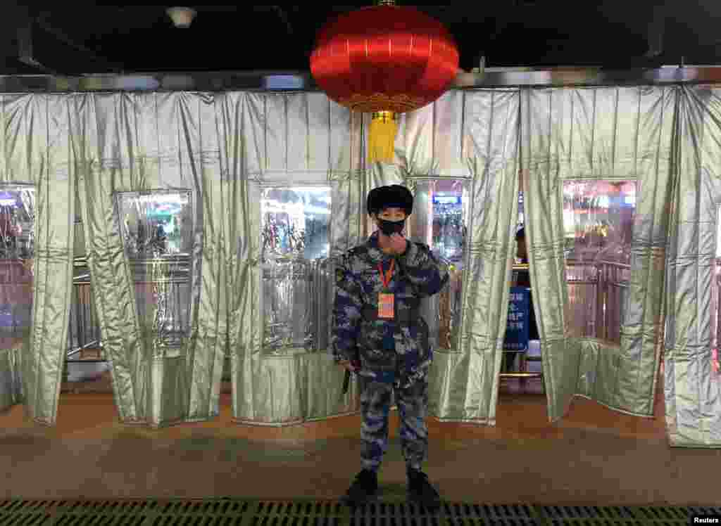 A Chinese security worker wearing a mask stands guard outside a checkpoint at the Beijing West Railway Station. (Reuters)
