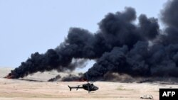 Smoke billows as a helicopter manoeuvres during the Northern Thunder military exercises in Hafr al-Batin, 500 kilometers north-east of the Saudi Capital Riyadh on March 10.