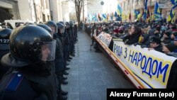 """Шерушілер парламент ғимаратын күзеткен полиция жасағына қарсы """"Парламент халықпен бірге"""" деген жазуы бар плакаттар алып шықты. Киеве, 3 желтоқсан 2013 жыл."""