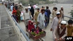 An Afghan man pushes a cart with a woman and children as they cross the border between Afghanistan and Pakistan in the Torkham (file photo).
