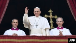 "Pope Francis (center) waves from the balcony of St Peter's Basilica in the Vatican during the traditional ""Urbi et Orbi"" Christmas message to the city and the world on December 25."
