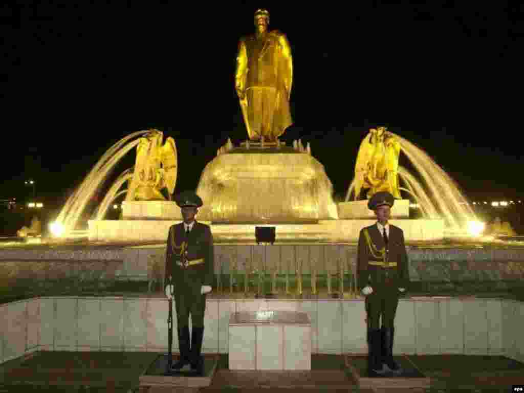 """An honor guard is permanently positioned in front of the statue of President Niyazov in downtown Ashgabat (epa) - Over his 20 years in power, Niyazov developed an extensive cult of personality. His books were required reading in all schools, and the state-controlled media was so full of fawning tributes that he regularly asked journalists to tone down their adoration. In October, five Ashgabat theaters were presenting plays based on his works. """"It is hard for me to listen to applause meant only for me,"""" Niyazov said."""