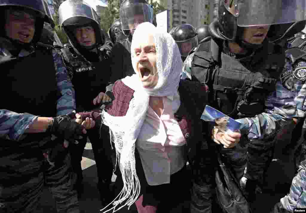 Ukrainian riot police detain an elderly Orthodox Christian activist as she protests against the gay-pride parade.