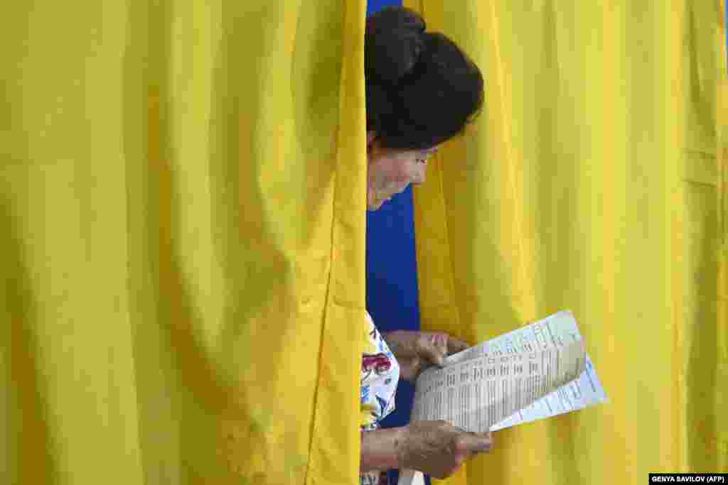 A woman looks through her ballot at a polling station in Kyiv.Voter turnout initially appeared lower than expected. (AFP/Genya Savilov)