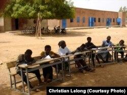 Күн ысыкта сыртта окуп жаткан балдар, Буркино Фасо