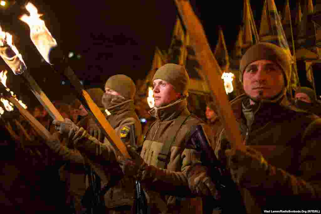Бійці полку «Азов», запаливши смолоскипи, стоять біля пам'ятника князю Святославу перед його урочистим відкриттям