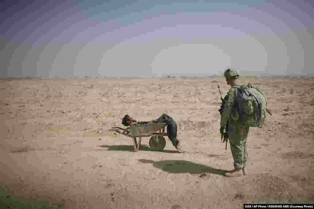 A U.S. soldier looks at the body of a suspected Taliban militant who was killed in a coalition missile strike in Zhari district, Kandahar Province, on October 10, 2010.