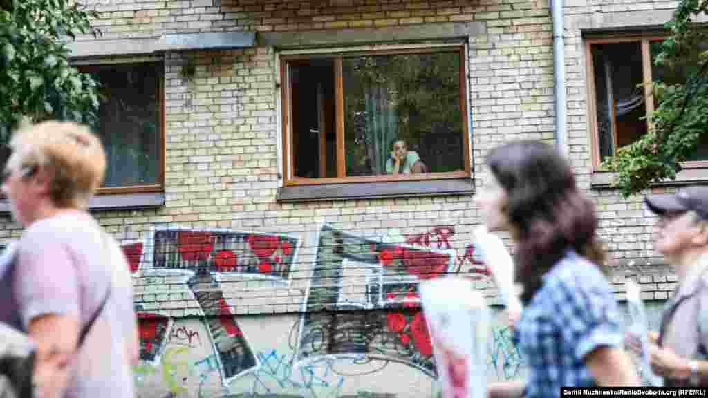 Женщина наблюдает за акцией из окна квартиры
