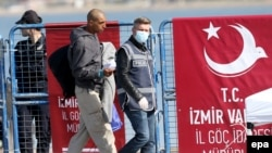 "A migrant is escorted by a Turkish police officer walking past a banner reading: ""Migration directorate of the Izmir Governor"" as they arrive by ferry from the Greek island of Lesbos at the Dikili harbor in Izmir on April 4."
