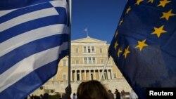 Афинадағы парламент алдында Грекия мен Еуропа Одағы туларын ұстап тұрған адам. (Көрнекі сурет)