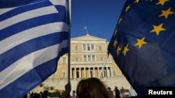 Человек держит флаги Греции и Европейского союза во время митинга у здания парламента в Афинах. 18 июня 2015 года. Иллюстративное фото.