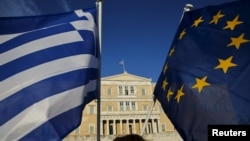 Greece -- Greece-EU-Eurozone-Debt-A woman waves a Greek national flag (L) and a European Union flag during a rally outside the parliament, in Athens June 18, 2015.