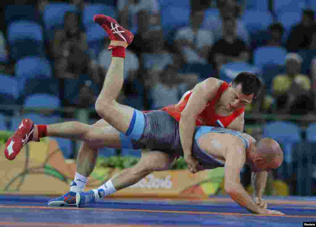 Russian wrestler Roman Vlasov (top) won gold for the second Olympics in a row, competing in the men's 75-kilogram Greco-Roman wrestling event.