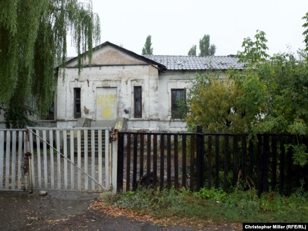 "A building on the grounds of School No. 32 in Pryvillia is spray-painted with the phrase ""Glory to Ukraine."""